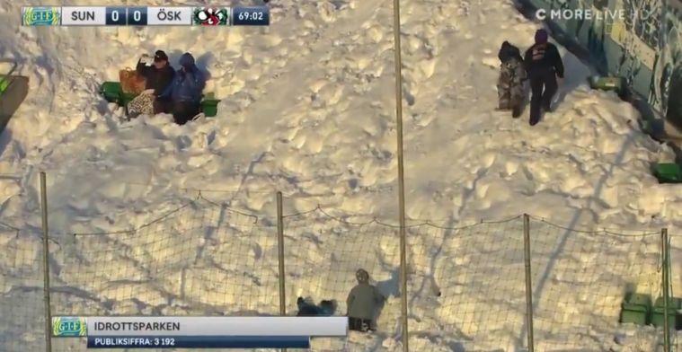 Zweedse fans glijden tijdens de wedstrijd over ondergesneeuwde tribunes
