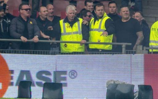 Afbeelding: Het loopt mis in Nederland: fans bestoken elkaar met vuurwerk, stoeltjes op veld